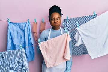 African american woman with braided hair washing clothes at clothesline puffing cheeks with funny face. mouth inflated with air, crazy expression.