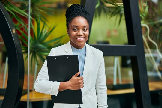 Young african american businesswoman smiling happy holding clipboard at the city.