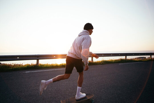 Millennial hipster man push to gain speed on skateboard. Man on longboard ride into sunset. Summer vibes, skateboarding lifestyle. Summertime activity, wanderlust travel blog