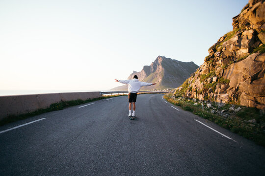Cinematic epic photo of young man in grey hoodie ride longboard on empty road in beautiful mountain landscape. Wanderlust travel concept. Millennial generation z adventure in summer. Sunset skating