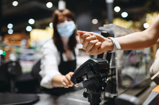 Cropped close up woman hand arm shopping at supermaket put smart watch to modern bank payment terminal process acquire payments near cashier checkout inside store. People lifestyle purchasing concept.