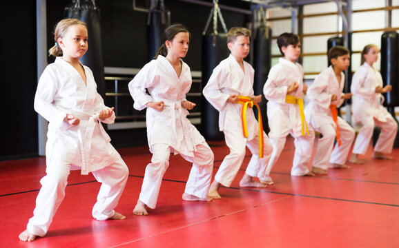 Preteen school childs together trying martial moves in karate class