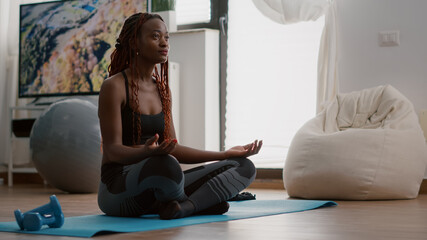 Flexible black athlete relaxing in lotus position on floor in living room enjoying healthy lifestyles. Fitness woman in sportwear streching muscle during strech gymnastics warming body