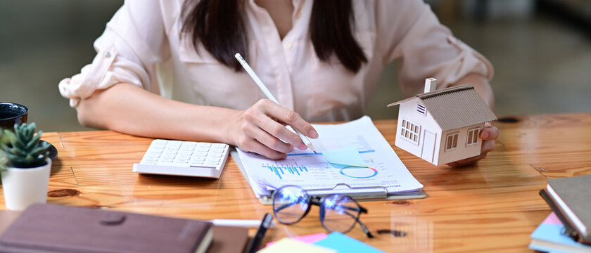 Women using calculator and planing business investment for real estate in the future.