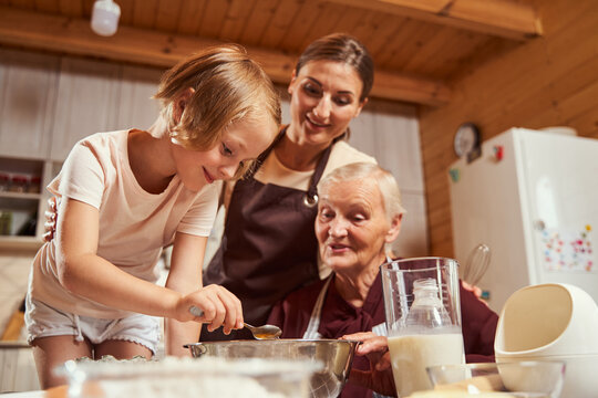 Child holding teaspoon above deep plate with her family watching