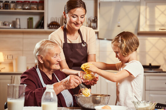 Girl placing dough mixture into glass bowl in mother hands