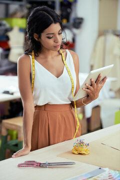 Pretty young serious seamstress reading comments of customer on tablet computer before starting to work on new dress