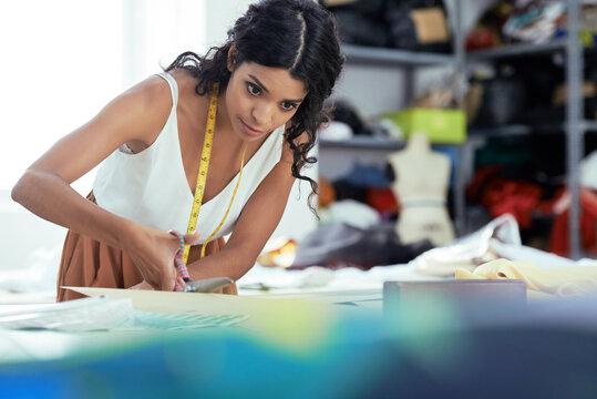Professional dressmaker sewing dress at her workshop for customer
