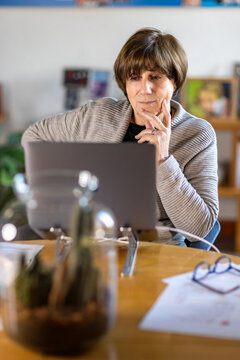 Elderly Psychologist and Senior Consultant working remotely from home in a video meeting with her laptop during quarantine or lockdown