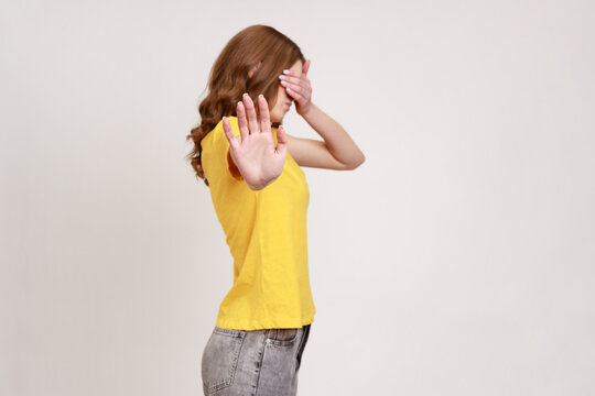 I'm not watching! Profile portrait of scared shamed teenager girl in casual yellow T-shirt covering eyes and showing stop gesture, hiding eyesight. Indoor studio shot isolated on gray background.