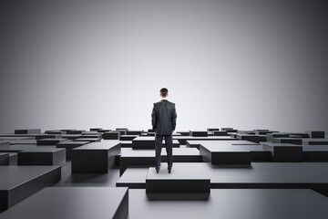 Businessman standing on abstract gray geometric maze background with mock up place. CEO and future...