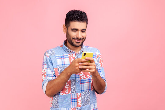 Portrait of attractive bearded man in blue shirt using mobile phone with happy expression, addicted to smartphone, texting in social network. Indoor studio shot isolated on pink background.