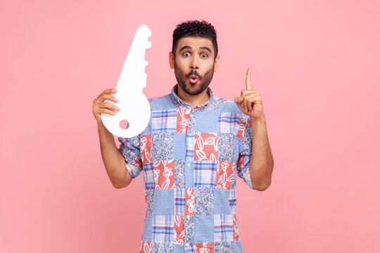 Young adult man with beard and dark hair wearing blue casual style shirt holding big paper key and pointing finger up, having idea for renting new flat. Indoor studio shot isolated on pink background.