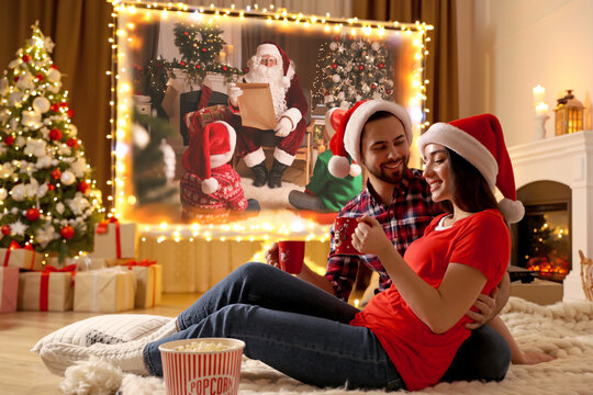 Couple watching movie on projection screen in room decorated for Christmas