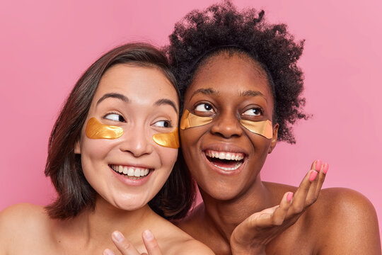 Portrait of carefree glad diverse female models apply anti aging moisturizing eye mask smile happily spend free time on caring about themselves stand closely have well cared body healthy skin