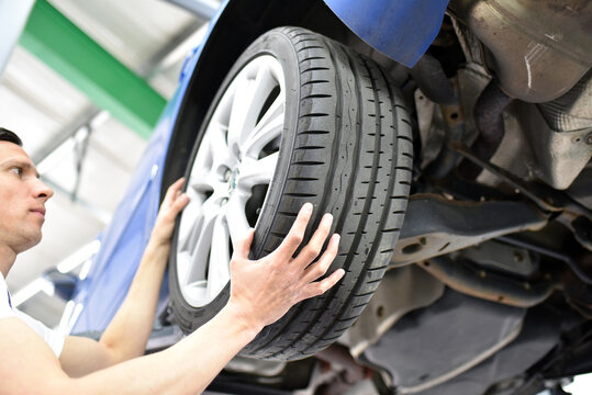 tyre change in a car repair shop - worker assembles rims on the vehicle