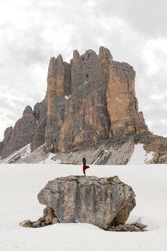 Traveler doing yoga in snowy mountains
