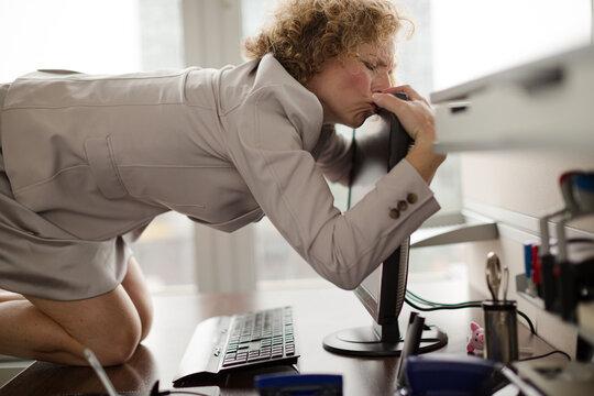 Businesswoman hugging computer at desk
