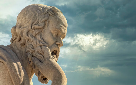 Socrates in deep thoughts, the ancient Greek philosopher marble statue under dramatic cloudy sky