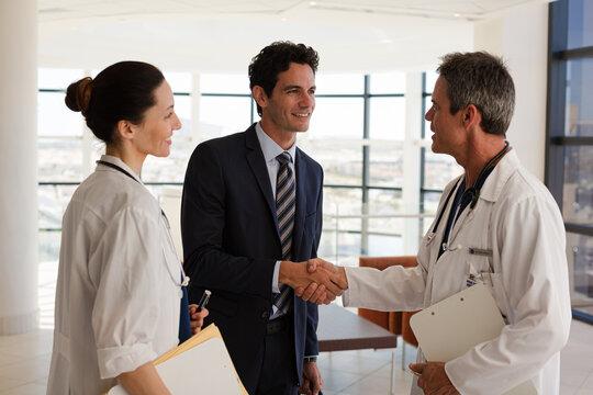 Doctor and businessman handshaking in meeting