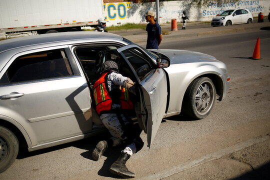 A member of the Mexican National Guard checks a car at a military checkpoint as part of a security operation to reduce violence in Ciudad Juarez