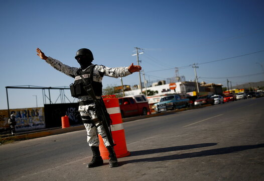 Members of the Mexican National Guard signs to stop a car at a military checkpoint as part of a security operation to reduce violence in Ciudad Juarez
