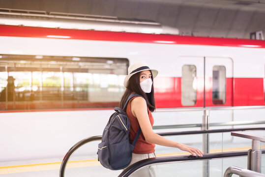 Asian woman wearing face mask and using escalator at train station,Safety on public transport,New normal during covid-19 pandemic
