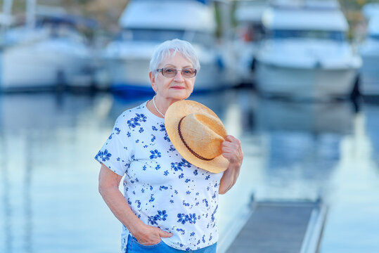 Attractive senior woman with hat and sunglasses at the harbour. Yachts and sailboat around her