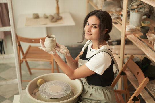 Woman showing handmade clay pot in workshop