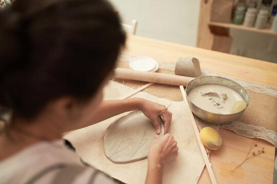 Ceramic artist shaping clay slab