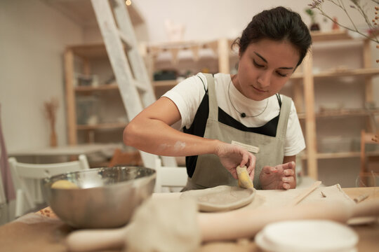 Artisan shaping clay plate with sponge