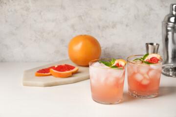 Glasses of tasty grapefruit margarita on light background