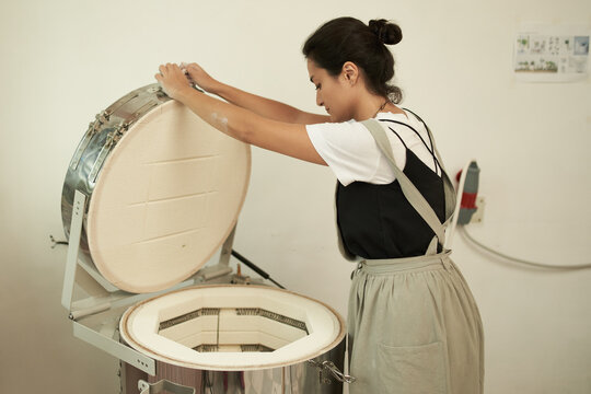 Artisan with electric oven in pottery workshop