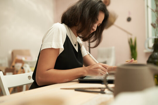 Ceramist creating new design on tablet