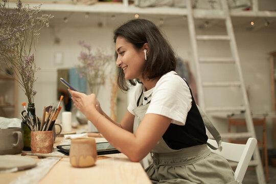 Female artisan using cellphone in pottery