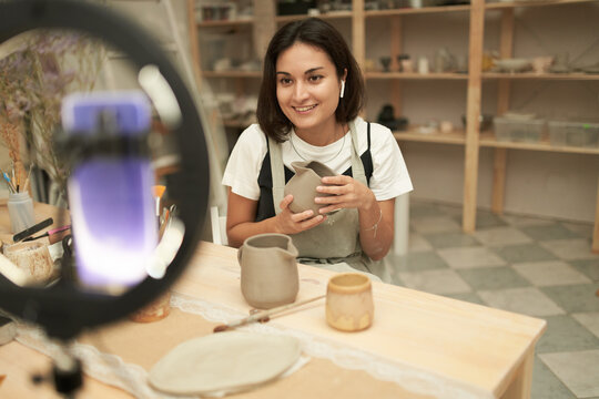 Friendly blogger showing handmade pitcher