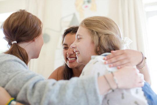 Three teenage girls embracing in bedroom