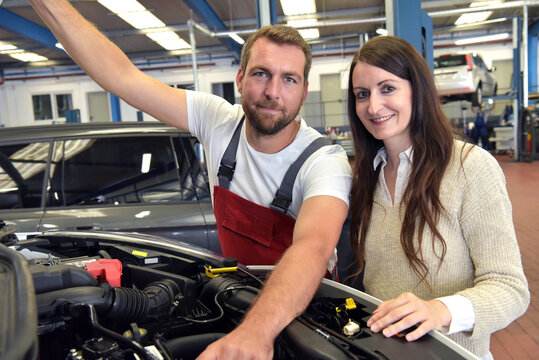 mechanic and customer talking in a workshop to repair a vehicle