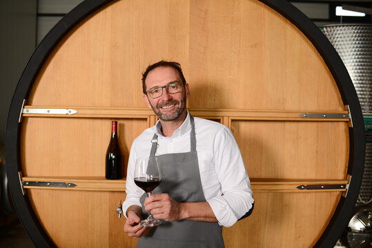 Portrait of a mature man oneologist tasting wine bottle in wine cellar with wooden barrel