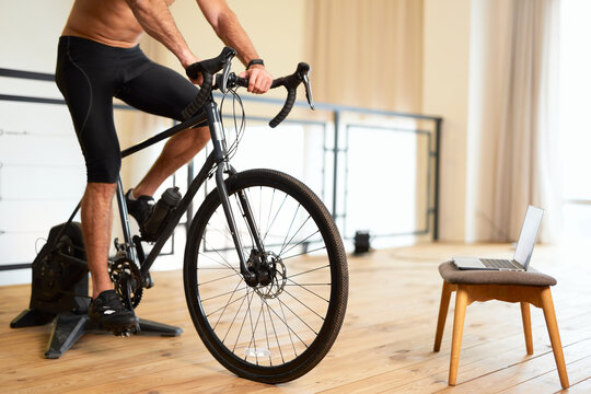 Athletic young man having stationery bike workout at home