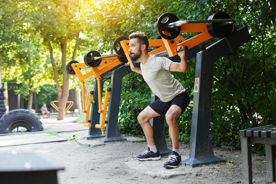 Open air gym. Street training on the municipal sports equipment. Athletic man doing squats using outdoor training machine.