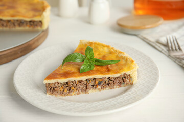 Piece of delicious pie with minced meat on white table