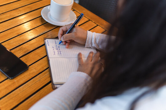 Anonymous woman writing in notepad in cafe