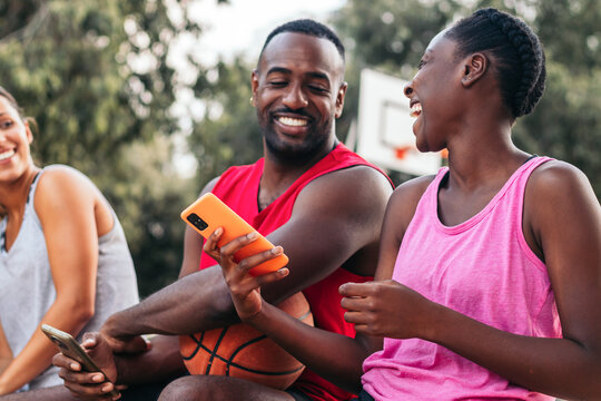 Cheerful diverse basketball players using smartphones on playground