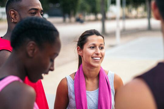 Joyful multiethnic sportspeople gathering on sports ground