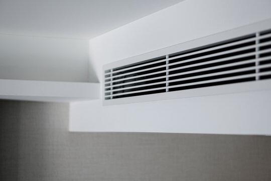 Air ventilator, metal slat frame on white ceiling.