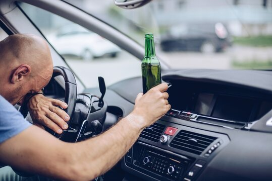 Drunk adult man drives a car with a bottle of beer. Driver under alcohol influence.