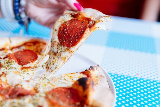 Image of woman's hand holding pizza slice at restaurant. Italian pizza.