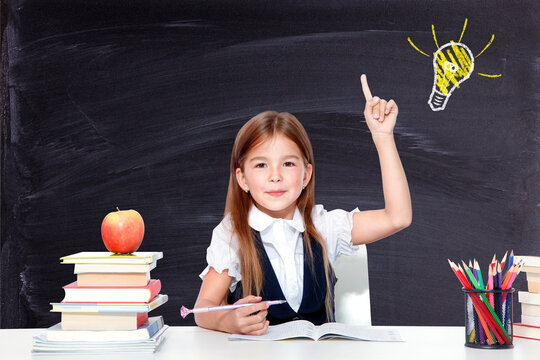 Young cute girl at chalkboard with light bulb over head