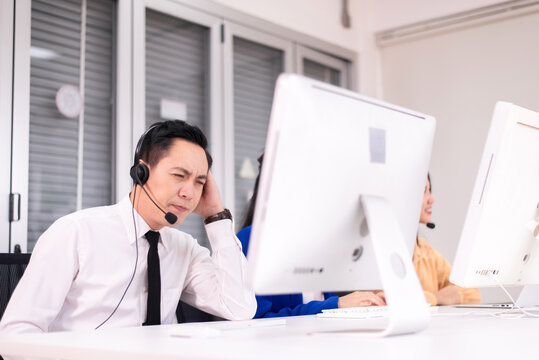 Stressed asian man customer service agent during working at call center service